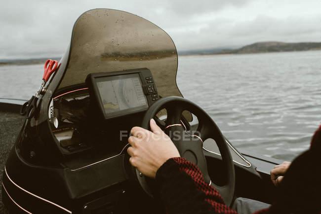 Personne sans visage retenant le volant de bateau naviguant le long de la route construite utilisant le navigateur par mauvais temps nuageux — Photo de stock