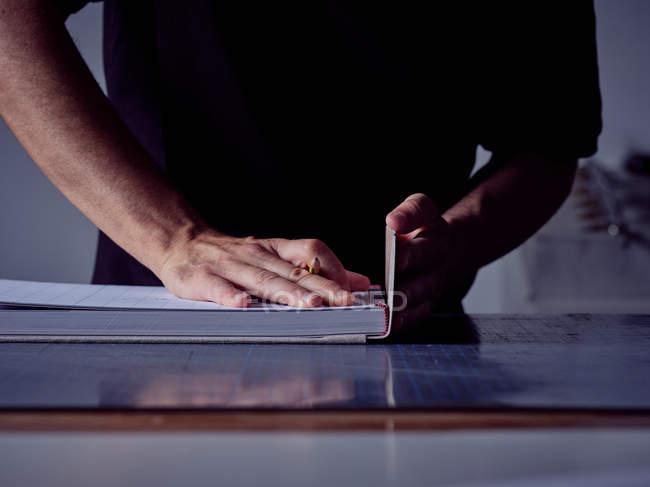 Руки ремесленника отделки связывающей книги склеивания твердого переплета рабочих за столом — стоковое фото