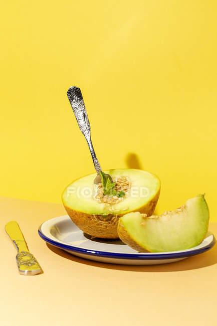 Corte maduro apetitoso melón picado dulce en el plato con cuchara y tenedor sobre fondo amarillo y naranja - foto de stock
