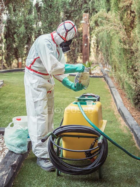 Fumigateur dans l'uniforme blanc et substance de fixation de masque respiratoire au-dessus du réservoir jaune dans la cour verte — Photo de stock