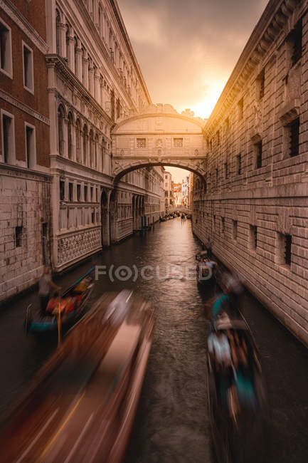 Navigazione che trasporta barche con passeggeri tra edifici antichi al tramonto della sera — Foto stock