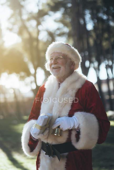 Веселий старший чоловік у костюмі Діда Мороза, стоячи з подарунком і дзвіночок в балакучих руках на фоні природи — стокове фото