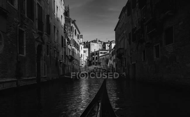 Golden bird gondola floating between old houses — Stock Photo
