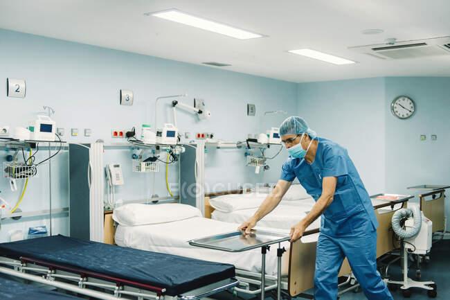 Медик в синей униформе и поднос для установки защитной маски на тележке в больничной палате на пустых кроватях — стоковое фото