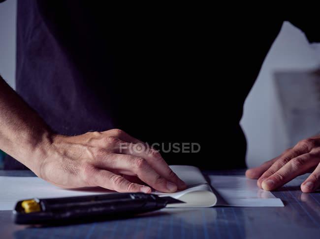 Mani di abili agili artigiani incollare le pagine insieme sul tavolo di lavoro — Foto stock