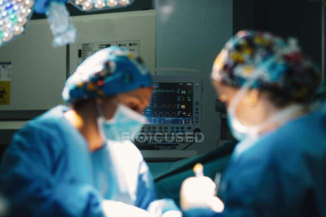 Серйозний молодий лікар у захисній масці та капюшоні робить операцію з інструментами та медсестрою. — стокове фото