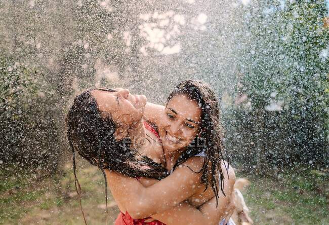 Friends in swimsuits hugging under water drops — Stock Photo