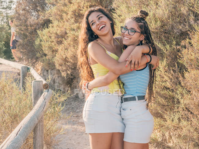 Cheerful smiling casual female friends hugging while standing on pathway in rural countryside on sunset — Stock Photo
