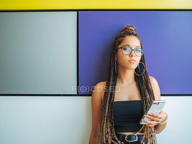 Pretty teenage girl with stylish dreadlocks using smartphone in colorful room — Photo de stock