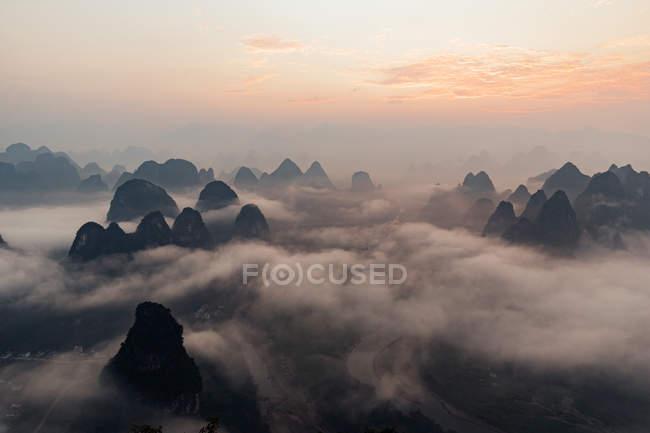 Misterioso paisaje fluvial entre altas montañas en neblina - foto de stock