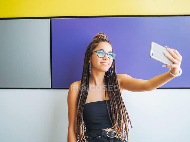 Pretty teenage girl with stylish dreadlocks taking selfie on smartphone in colorful room — Photo de stock