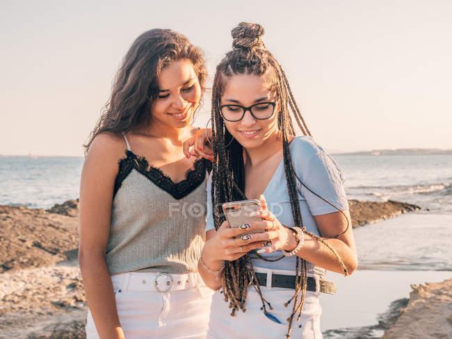 Восхитительные счастливые случайные женщины, просматривающие смартфон, стоя на берегу моря на закате — стоковое фото