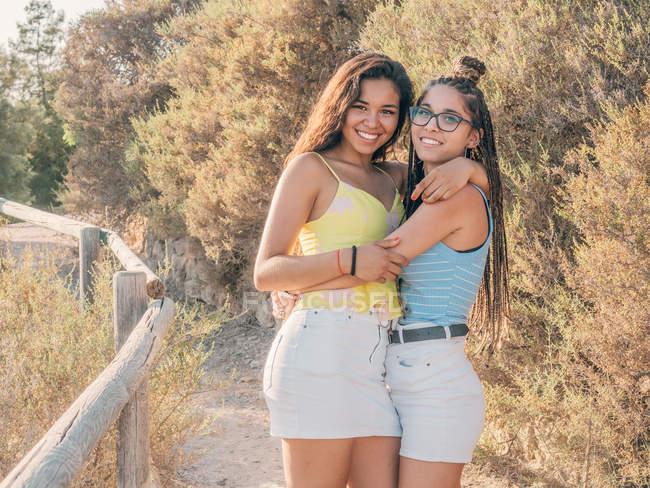 Feliz moda jovens mulheres de ligação no campo — Fotografia de Stock