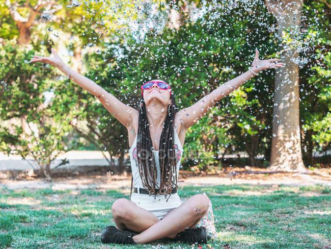 Joyeuse jeune femme avec des dreadlocks assis sur les jambes au sol croisés jetant des confettis colorés et levant les yeux — Photo de stock