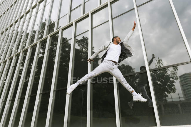 Вид сбоку красивого афроамериканского бизнесмена, празднующего победу, поднимающего руку и прыгающего высоко на фоне стеклянной стены — стоковое фото