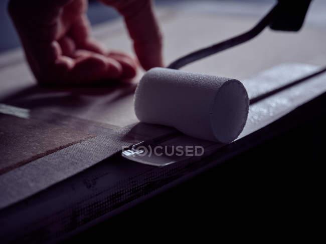 Рука профессионального ремесленника применения клея с белым роликом на краю картонной крышки для книги — стоковое фото