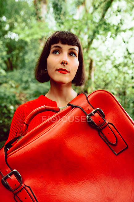 Woman in red with big red suitcase walking in green forest — Stock Photo