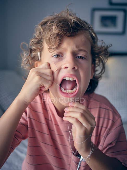Капризный малыш, запутавшись в зубной щетке, делает лица, утомляя себя зубами, чтобы вытащить ее, глядя в сторону — стоковое фото