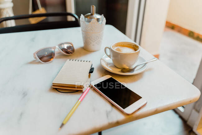 White smartphone and cup with coffee on marble table in cafe with small notepad and stylish sunglasses — Stock Photo