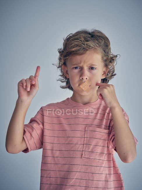 Bimbo riccio pensoso tacere con intonaco sulla bocca mentre punta il dito nell'aria chiedere di parlare e guardare la fotocamera — Foto stock