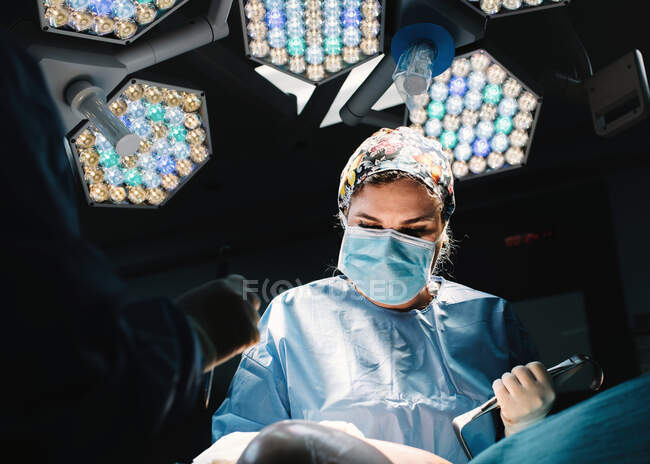 From below serious young doctor in protective mask and cap making surgery with instruments and crop nurse — Stock Photo