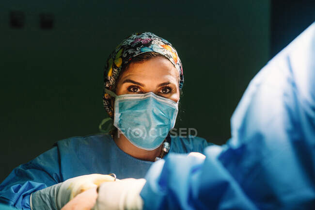 Serious young doctor in protective mask and cap making surgery with instruments and crop nurse — Stock Photo