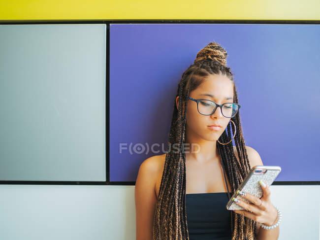 Jolie adolescente avec dreadlocks élégants en utilisant smartphone dans la chambre colorée — Photo de stock