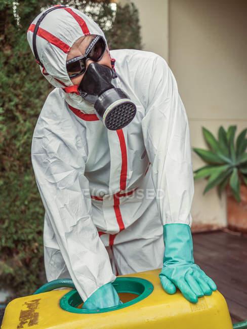 Especialista em uniforme para fumigação segurando carrinho amarelo no quintal — Fotografia de Stock