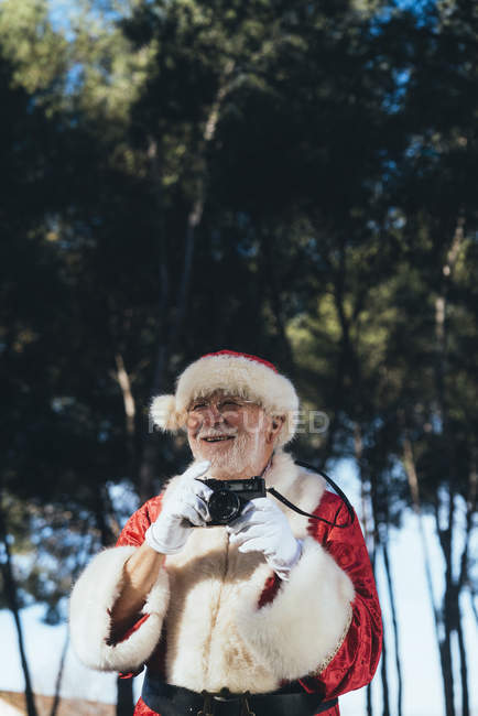Посміхаючись старший чоловік у костюмі Санта-Клауса стоячи і фотографувати з камерою на фоні природи — стокове фото