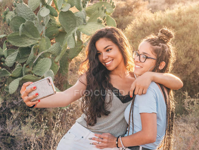 Smiling trendy young women taking selfie at countryside — Stock Photo