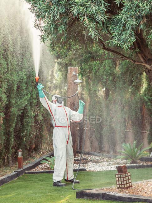 Fumigator in white uniform spraying substance on garden — Stock Photo