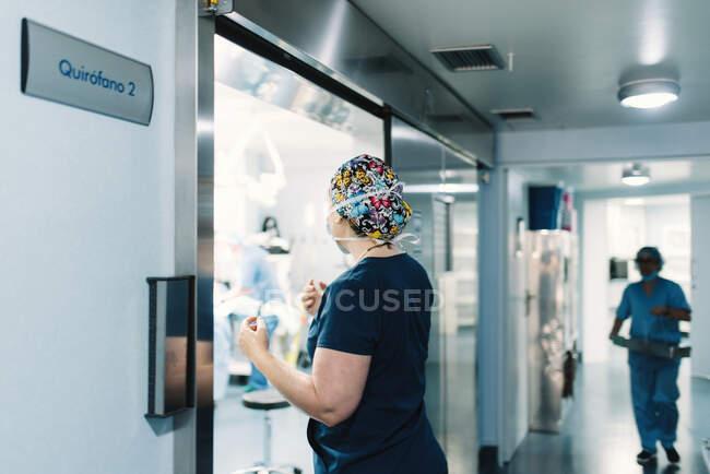 Vista lateral de la mujer en uniforme azul y máscara protectora que viene en el quirófano y enfermera caminando a lo largo del pasillo - foto de stock