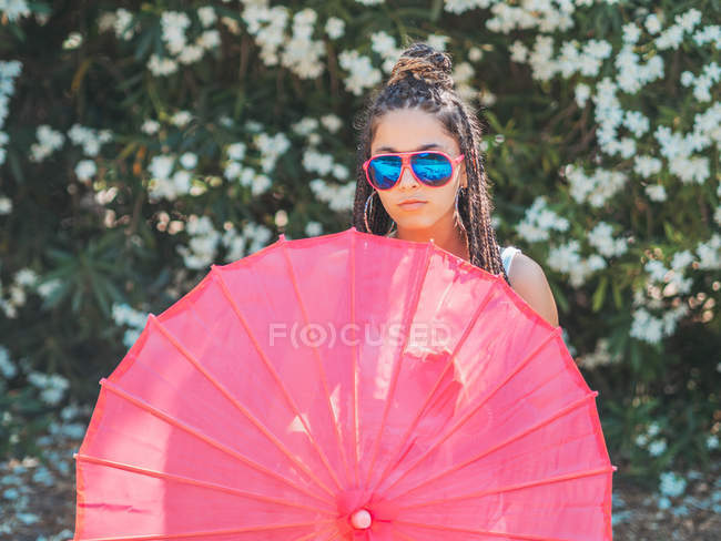 Slim young woman in sunglasses with umbrella standing near blooming trees — Stock Photo