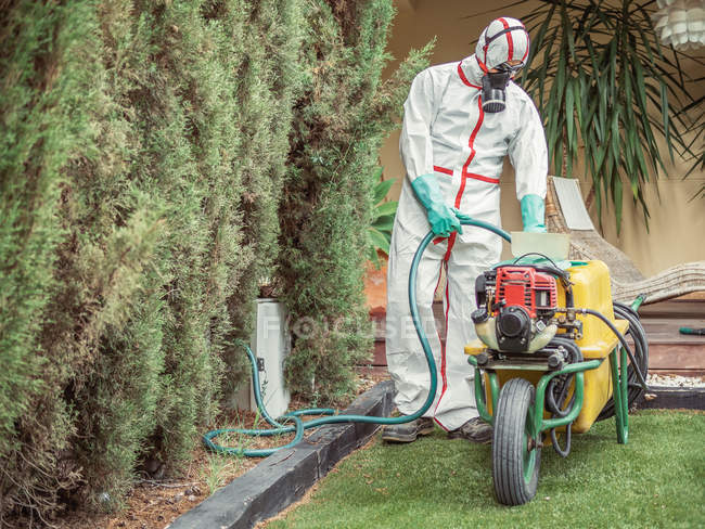 Man in uniform for fumigation and respiratory mask taking green hose from yellow tank on wheel for disinfection process — Stock Photo