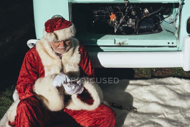 Людина в костюмі Діда Мороза текстових повідомлень на мобільному телефоні, сидячи в Ван з відкритим моторному відсіку — стокове фото