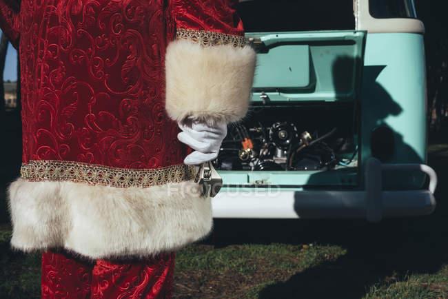 Невпізнанний людина в червоному і білому костюмі Діда Мороза оглядає двигун Vintage зелений Ван в сонячний день — стокове фото