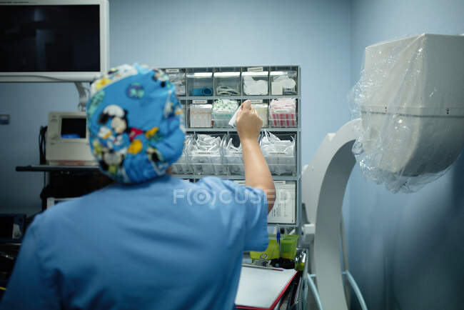 Back view of female medic in blue uniform taking supplies necessary for surgery in hospital — Stock Photo