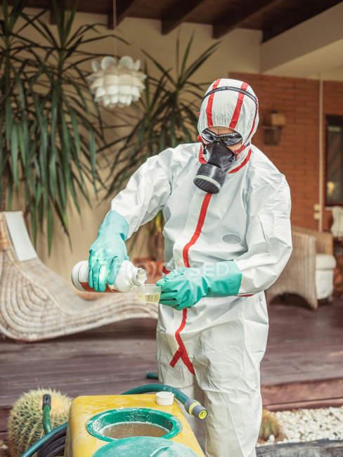 Fumigateur professionnel en uniforme pour la fumigation préparant la solution chimique pour la pollinisation dans la cour de maison — Photo de stock