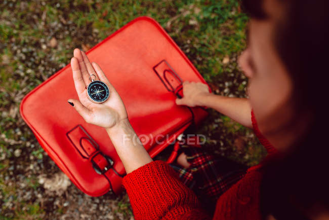 Closeup of compass in hand of woman with bright red suitcase on ground with grass — Stock Photo