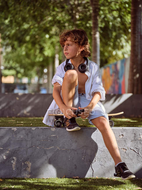 Casual pensive boy in headphones using mobile phone sitting on skateboard — Stock Photo