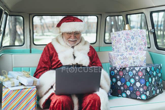 Весела людина в костюмі Діда Мороза сидить у фургоні з ноутбуком і яскравими подарунками в сонячний день — стокове фото