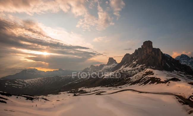 Majestic snow valley con montagne scure illuminate dal sole sotto il cielo nuvoloso a contrasto nelle Dolomiti — Foto stock