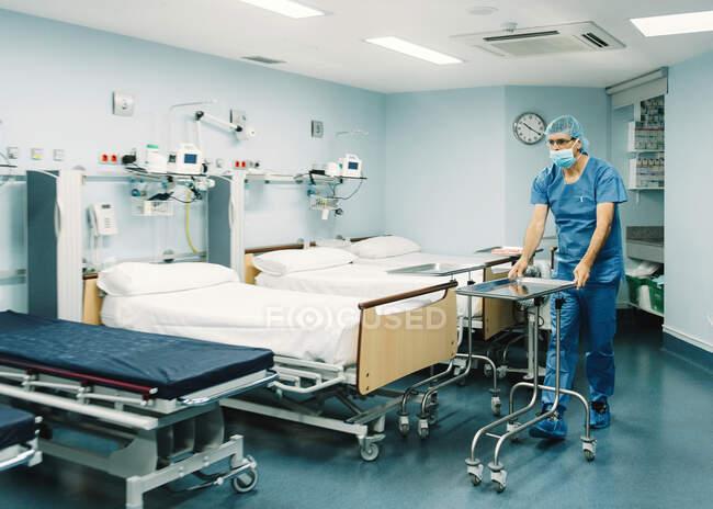 Лікарня в синьому мундирі і захисна маска на тролейбусі в лікарняній палаті. — стокове фото