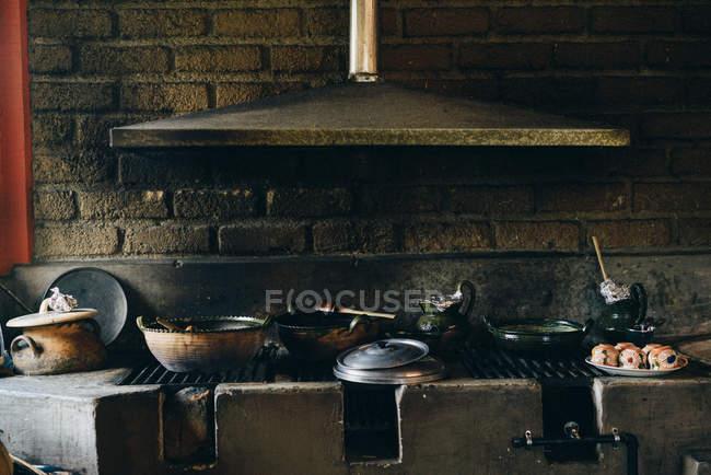 Calefator de pedra sujo velho com potenciômetros gastos e sistema de ventilação sobre a parede de tijolo na luz do dia — Fotografia de Stock
