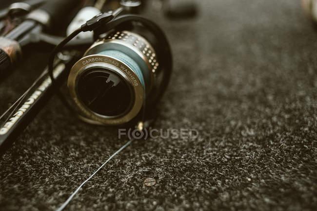 Caña de pescar con carrete de pesca brillante con cubierta negra y línea fuerte azul para la pesca en guijarros - foto de stock