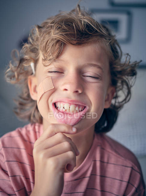 Unsteady baby tooth in wide open mouth of anonymous child pulling lip down to show tooth with closed eyes — Stock Photo