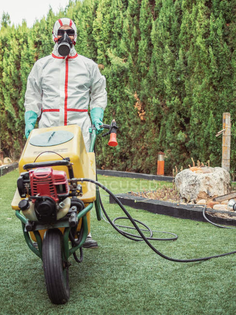 Specialist in uniform for fumigation holding yellow trolley in yard — Stock Photo