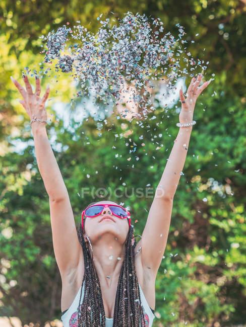 Fêmea nova alegre com dreadlocks que jogam o confetti colorido e que olham acima — Fotografia de Stock