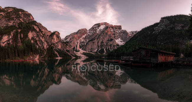 Houseboat surrounded with mountains on serene lake — Stock Photo