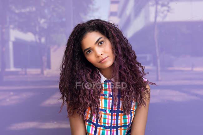 Porträt einer nachdenklichen jungen Frau mit lockigem Haar, die den Kopf neigt und gegen eine Glaswand in die Kamera blickt — Stockfoto
